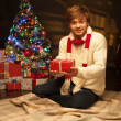 Young smiling man holding red christmas gift — Stock Photo
