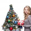Young smiling woman holding christmas gift — Stock Photo