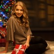 Young smiling woman holding red christmas gift — Stock fotografie