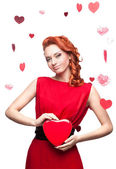 Smiling red-haired girl holding red heart — Stock Photo
