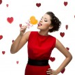 Young cheerful woman licking lollipop — Stock Photo