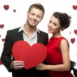Young couple holding sign in form of red heart — Stock Photo #15718601