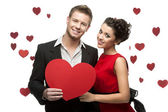 Young couple holding sign in form of red heart — Stock Photo