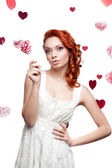 Surprised red-haired woman holding lollipop — Stock Photo