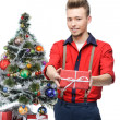 Young smiling vintage man holding gift near christmas tree — Stock Photo