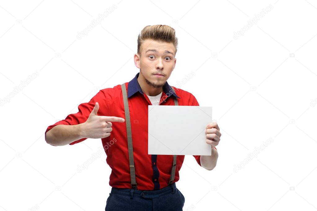 Cheerful young caucasian man in red vintage clothing holding and pointing on sign isolated on white — Stock Photo #17609283