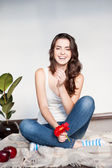 Smiling casual brunette girl holding red flower — Stock Photo