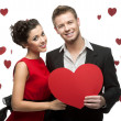 Young smiling caucasian couple holding red heart — Stok fotoğraf