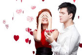 Young smiling couple holding small red gift — Stock Photo