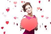 Brunette woman holding big red paper heart — Stock fotografie