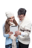 Young smiling winter couple using tablet — Stock Photo