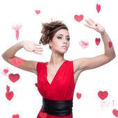 Kırmızı kalpler arka plan üzerinde kırmızı elbiseli kadın — Stok fotoğraf