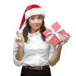 Young cheerful businesswoman in santa hat holding christmas gift — Stock Photo #47641157