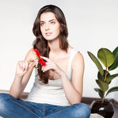 Thoughtfulcasual brunette girl holding red flower — Stock Photo