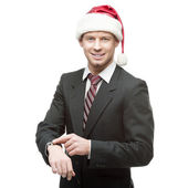 Young smiling businessman in santa hat pointing at watch — Foto de Stock