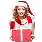 性格开朗的年轻美女在圣诞老人的帽子,拿着礼物 — 图库照片