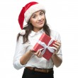 Young cheerful businesswoman in santa hat holding gift on white — Stock Photo #48282395