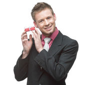 Businessman holding small red gift — Stock Photo