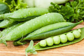 Green peas pods lying with greenery — Stok fotoğraf