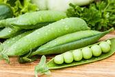 Gousses de pois verts parsemée de verdure — Stockfoto