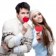 Cheerful casual young couple holding red hearts — Stock Photo #49003407