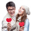 Young cheerful casual couple holding red hearts — Stock Photo #49003411