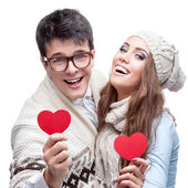 Young cheerful casual couple holding red hearts — Stock Photo