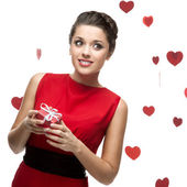 Caucasian woman in red dress holding gift — Stock Photo