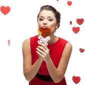 Kaukaski kobieta w czerwonej sukience gospodarstwa lizak — Zdjęcie stockowe