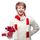 Young winking man holding christmas gifts — Stock Photo