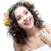 Smiling young woman with flower in hair — Stock Photo