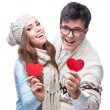 Cheerful casual young couple holding red hearts — Stock Photo #50322573