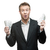 Young surprised businessman holding money — Stock Photo