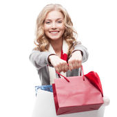 Young cheerful woman holding shopping bags — Stock Photo