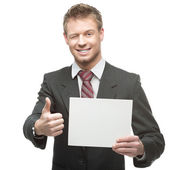 Cheerful winking businessman holding sign — Stock Photo