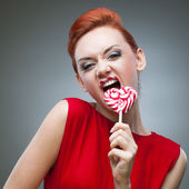 Funny red-haired girl holding candy — Stock Photo