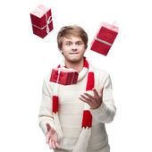 Young funny man juggle the christmas gifts — Stock Photo