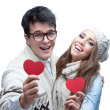 Young cheerful casual couple holding red hearts — Stock Photo #50686195