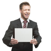 Young winking businessman holding sign — Stock Photo