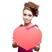 Cheerful young woman holding red paper heart — Stock Photo