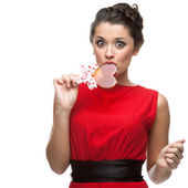 Caucasian woman in red dress licking lollipop — Stock Photo