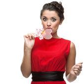 Caucasian woman in red dress licking lollipop — Foto de Stock