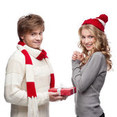 Cute man presenting christmas gift to woman — Stock Photo