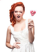 Winking red woman holding lollipop — Stock Photo