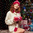 Young woman holding red gift over christmas tree and lights on b — Stock Photo #51342051