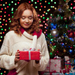 Young woman holding red gift over christmas tree and lights on b — Stock Photo #51342171