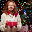 Young woman holding red gift over christmas tree and lights on b — Stock Photo #51342203