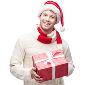 Young casual man in santa hat hoding christmas gift — Stock Photo