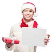 Young casual man in santa hat hoding sign and christmas gift — Stock Photo