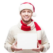 Young casual man in santa hat hoding sign — Stock Photo